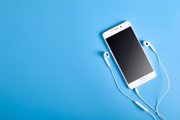 Handykopfhörer und ein handy der weißen farbe auf einem blauen hintergrund in den hellen farben mit einem platz für text.