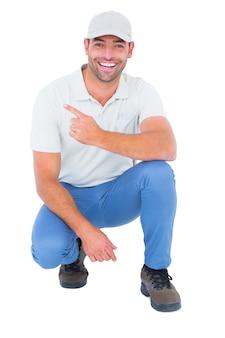 Handymaker duckend beim zeigen auf weißen hintergrund