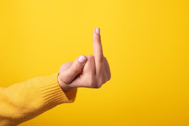 Handzeichen, das mittelfinger auf unhöfliche weise zeigt, was ficken über gelbem hintergrund bedeutet