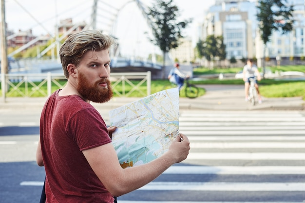 Hansome mann mit großem bart im roten t-shirt spaziergang in der stadt, um mehr darüber zu erfahren
