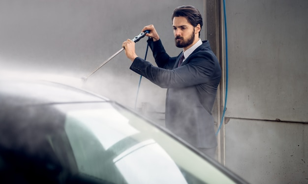 Hansome stilvoller junger bärtiger mann im anzug, der sein auto an der selbstbedienungsstation der manuellen autowäsche wäscht