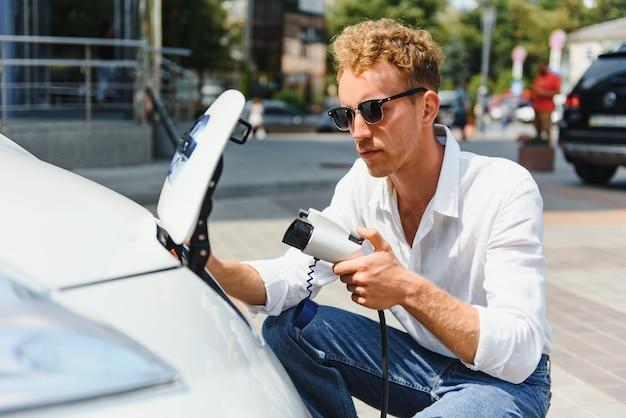 Hansome-typ sitzt in der nähe seines neuen modernen elektroautos und hält den stecker des ladegeräts, während das auto an der ladestation lädt