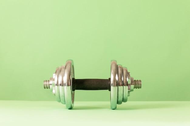 Hantel für bodybuilding auf grünem hintergrund. fitness gesund und sportkonzept