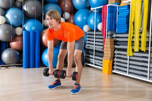 Hantel kreuzheben blonder mann im fitnessstudio gewichtheben