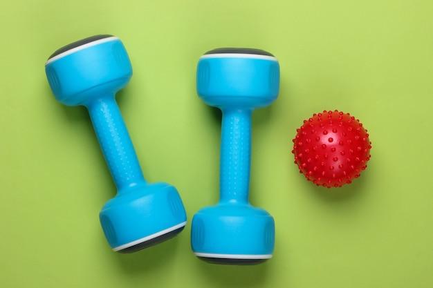 Hantel mit massageball auf grün. fitness, gesunder lebensstil konzept