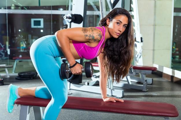 Hantel-trizeps-kickback-mädchenübung im fitnessstudio