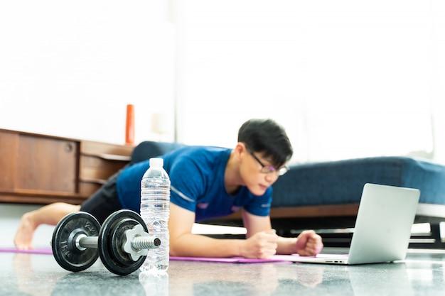 Hantel und reifer asiatischer mann, der übungen zu hause macht. training zu hause. soziale distanzierung.