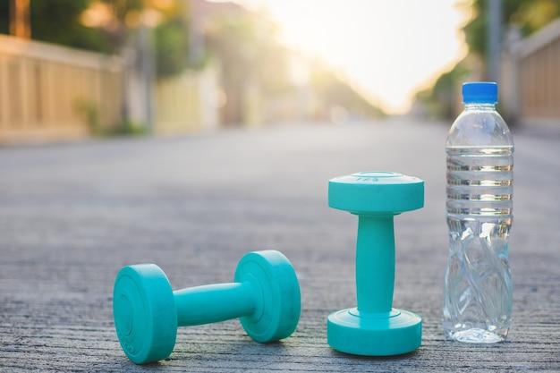 Hantelgewichte und flasche auf der straße