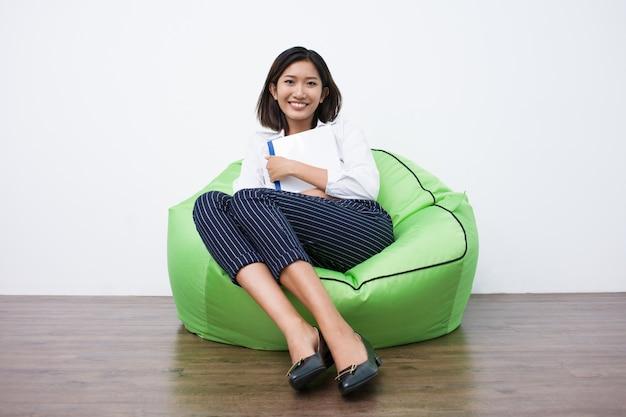 Happy asian weibliche studenten auf dem sitzsack ruht