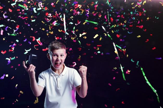 Happy boy mit gamepad und fliegenden konfetti