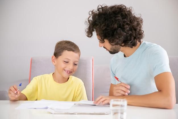 Happy boy und sein vater erledigen gemeinsam die hausaufgabe in der schule, schreiben in zeitungen und besprechen die lektion. konzept der familie und der schwulen eltern
