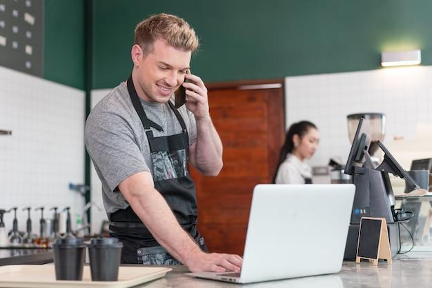 Happy cafe owner barista erhält bestellung vom kunden auf dem smartphone, während er den computer beim kaffee benutzt