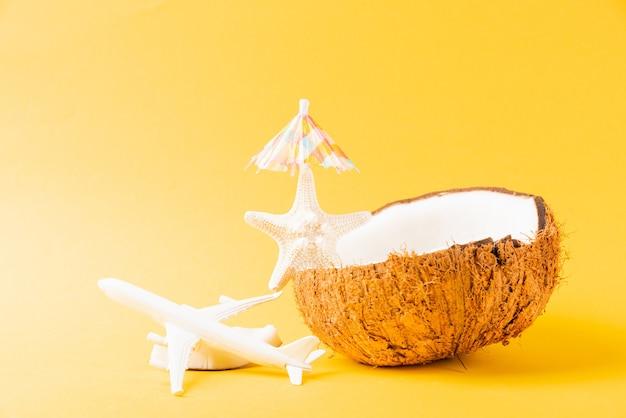 Happy coconuts day konzept frische kokosnuss seestern flugzeug flugzeug und sonnenschirm sun