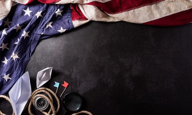 Happy columbus day konzept vintage amerikanische flagge kompass papierboot seil auf dunklem stein
