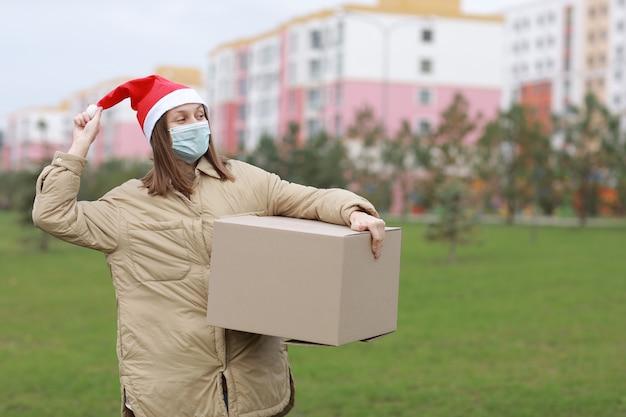 Happy delivery frau in einem roten weihnachtsmannhut und einer medizinischen schutzmaske hält eine große kiste im freien