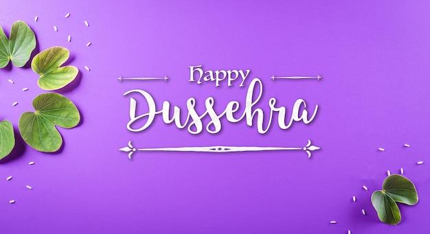 Happy dussehra grünes blatt und reis mit dem text auf violettem pastellhintergrund