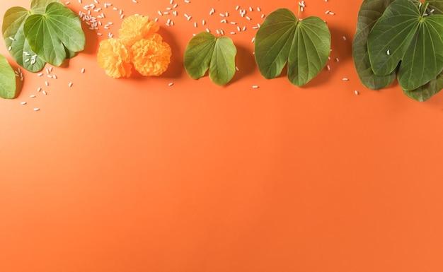 Happy dussehra yellow blüht grünes blatt und reis auf orangem hintergrund