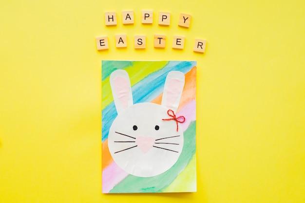 Happy easter text holzbuchstaben und handgemachte osterkarte auf gelbem hintergrund.