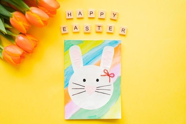 Happy easter text holzbuchstaben und handgemachte osterkarte und orange tulpen auf gelbem hintergrund.