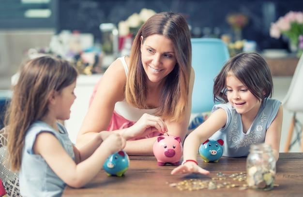 Happy family mutter tochter spart geld sparschwein zukünftige investitionseinsparungen.