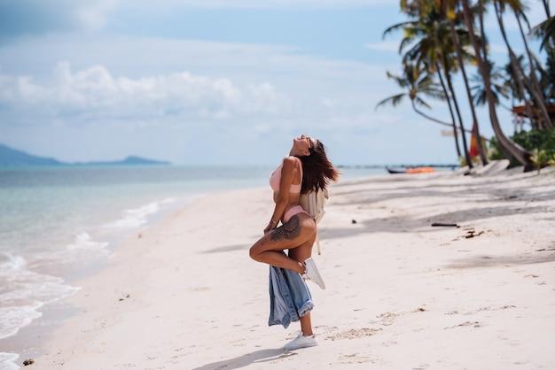 Happy fit hübsche gebräunte sportlich tätowierte frau am strand mit jeansjacke