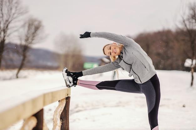 Happy fit sportlerin, die an schneebedeckten wintertagen dehnungs- und aufwärmübungen in der natur macht