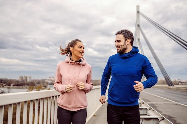 Happy fit sportliche heterosexuelle freunde laufen auf der brücke und plaudern. outdoor-fitness auf bewölktem wetterkonzept. städtisches leben.