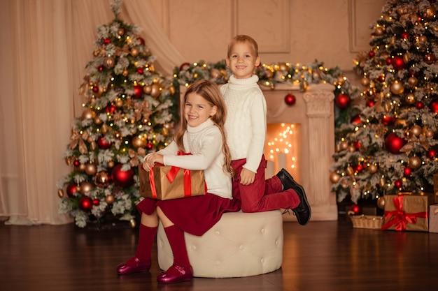 Happy gemini bruder und schwester geben sich zu hause in der nähe des kamins und des neujahrsbaums ein neujahrsgeschenk
