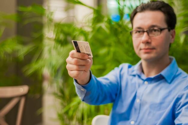 Happy geschäftsmann übergeben seine kreditkarte an kellner im café. geschäftsmann bezahlt mit einer kredit- oder debitkarte
