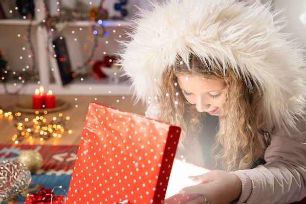 Happy girl öffnet eine weihnachtsgeschenkbox in weihnachtsstimmung