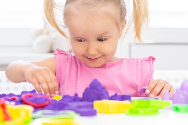 Happy girl spielt kinetischen sand. blondes schönes mädchen lächelt und spielt mit lila sand auf einem weißen tisch