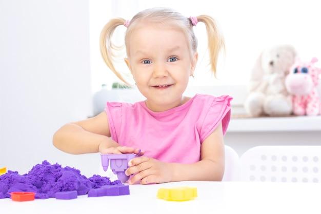 Happy girl spielt kinetischen sand in quarantäne. blondes schönes mädchen lächelt und spielt mit lila sand auf einem weißen tisch.