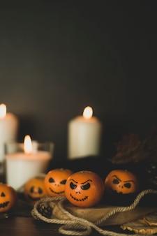 Happy halloween citrus, mandarinen mit gruseligen, lustigen gesichtern bemalt. dunkles foto mit kerzen. alternativen zu traditionellen halloween-kürbissen.