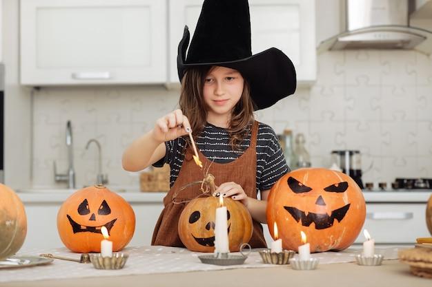 Happy halloween nettes kleines mädchen im hexenkostüm mit schnitzendem kürbis glückliche familie, die sich auf halloween-mädchen vorbereitet, zündet kerzen an