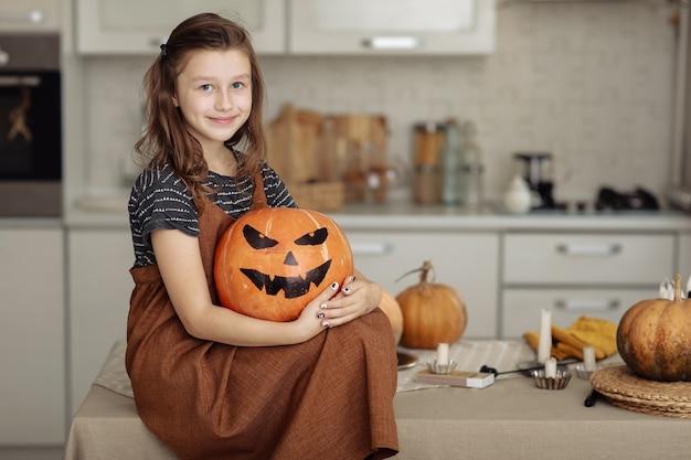 Happy halloween süßes kleines mädchen im hexenkostüm mit schnitzendem kürbis glückliche familie, die sich auf halloween vorbereitet