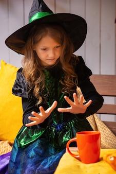 Happy halloween süßes lachendes kleines mädchen in hexenkostümen feiern halloween