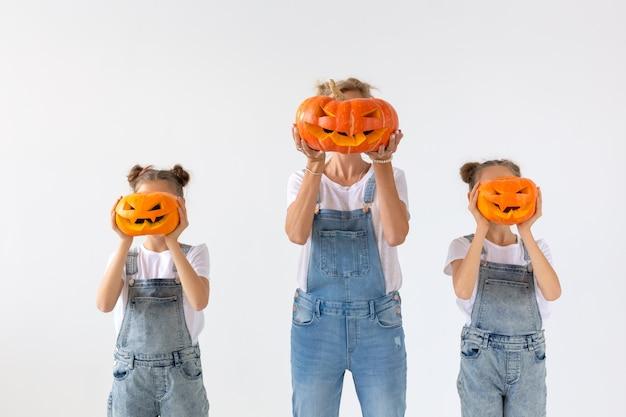 Happy halloween und feiertagskonzept - eine mutter und ihre töchter mit kürbissen. glückliche familie, die sich auf halloween vorbereitet.
