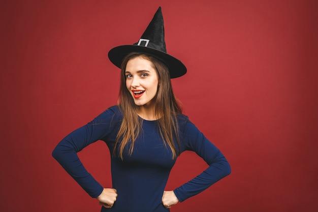 Happy halloween witch mit hellem make-up und langen haaren. schöne junge überraschte frau, die im sexy kostüm der hexen aufwirft. auf rotem hintergrund isoliert.