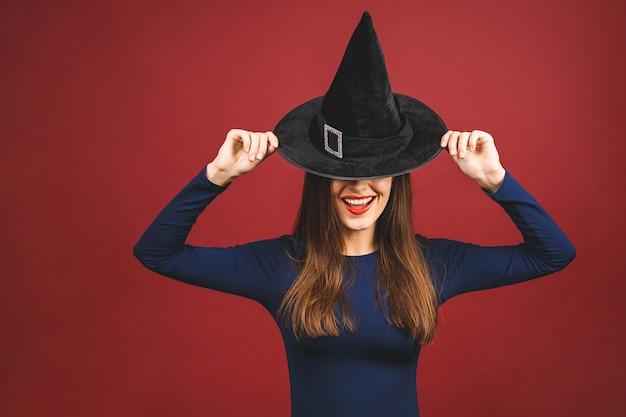 Happy halloween witch mit hellem make-up und langen haaren. schöne junge überraschte frau, die im sexy kostüm der hexen aufwirft. isoliert auf rotem hintergrund.