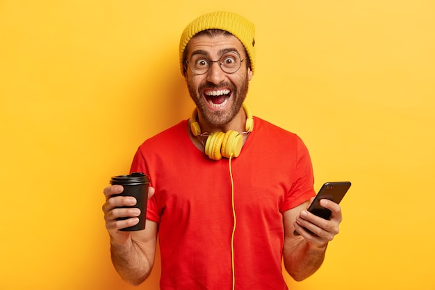 Happy hipster schafft neues profil in sozialen netzwerken, lacht vor glück, hält moderne elektronische geräte, trinkt kaffee
