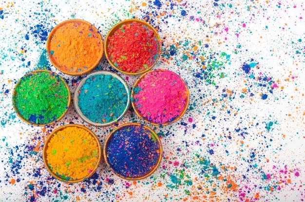 Happy holi draufsicht auf bunte holi-farben in schalen mit splash