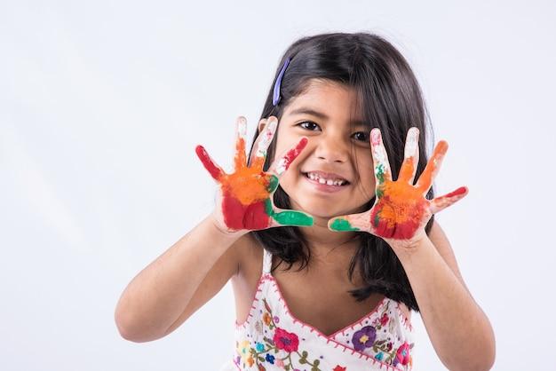 Happy holi gruß - nettes kleines indisches mädchen mit bunten händen, isoliert auf weißem hintergrund
