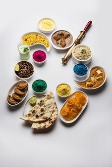 Happy holy konzept, das indische mittagsgerichte wie hühnchen paneer butter masala naan jeera reis black chana fry jalebi ras malai thandai und farsan mit holi-farben und pichkari zeigt