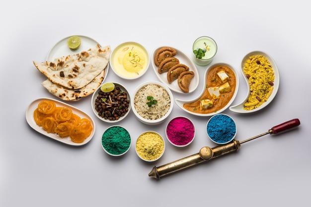 Happy holy konzept zeigt indisches mittagessen wie paneer butter masala naan jeera reis black chana fry jalebi ras malai thandai und farsan mit holi-farben und pichkari