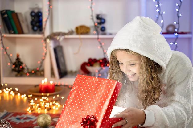 Happy kid mädchen mit geschenkbox in weihnachtsatmosphäre