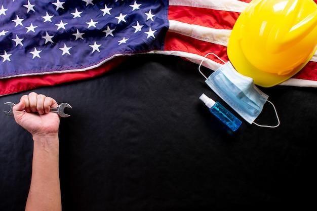 Happy labour day und gesundheitsversorgung durch covid-19-pandemie. medizinische maske, händedesinfektionsmittel. amerikanische flagge