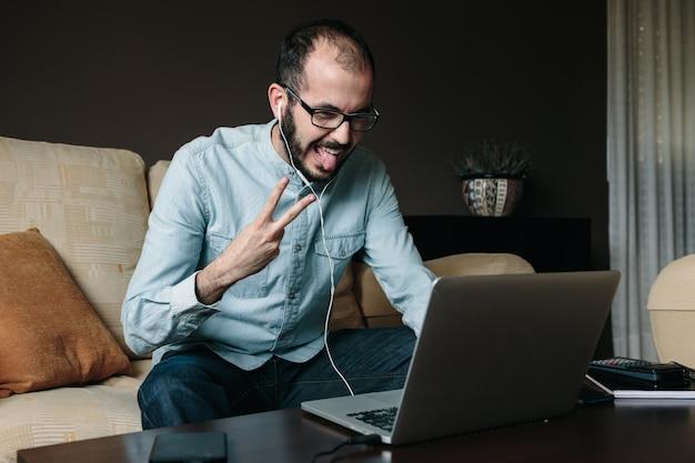 Happy man videokonferenzen und spaß mit seinen kollegen bei der arbeit von zu hause aus.
