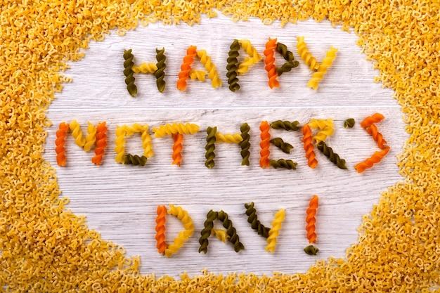 Happy mother's day pasta inschrift. wörter aus fusilli-nudeln. kreative begrüßung durch essen. ungewöhnliche überraschung für mama.