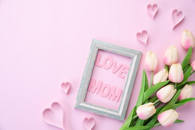 Happy muttertag konzept. rosa tulpenblume mit papierherzen und bilderrahmen