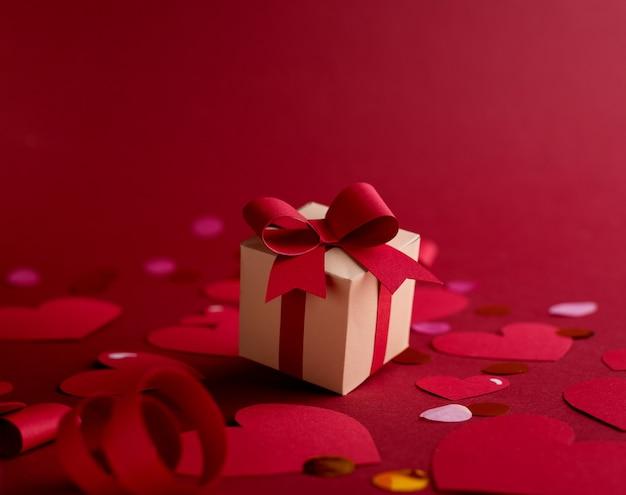 Happy st. valentinstag-konzept mit bastelpapier-geschenkbox, roten papierherzen, schleifen